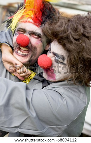 Unsure To Cuddle Or Strangle Each Other A Clown Couple Play Fight In A Funny Wrestling Altercation Of Love And Hate Known As A Lovers Tiff - stock photo