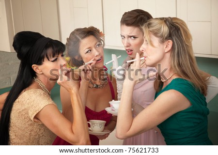 Unsure young woman around older ladies smoking in the kitchen - stock photo