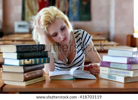 Untidy girl reading a book at a table in the library