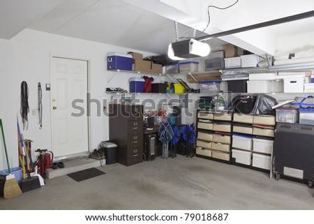 Untidy suburban garage with shelves and storage.