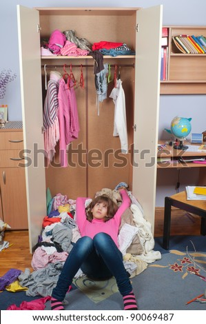 Untidy teenage girl lying on pile of wrinkled clothes inside her wardrobe and daydreaming - stock photo