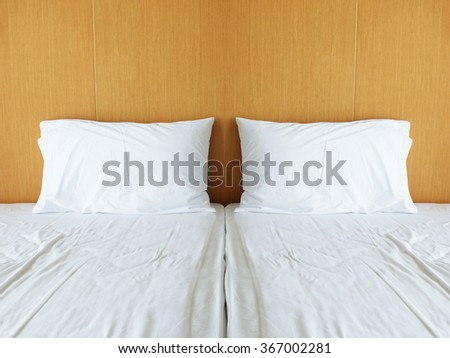 Untidy white bedding sheets and pillows in morning light - stock photo