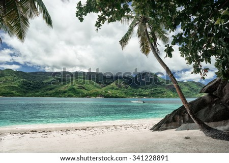 Untouched tropical beach with huge stones, cloudy sky  / outdoors photo of picturesque Seychelle islands. High resolution product. - stock photo