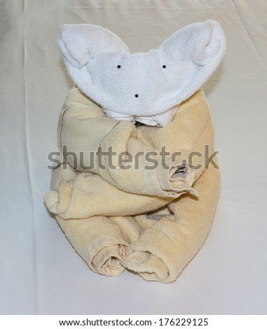 Unusual animal shaped like a koala or teddy bear created from rolled and folded towels on top of bed sheets in hotel - stock photo