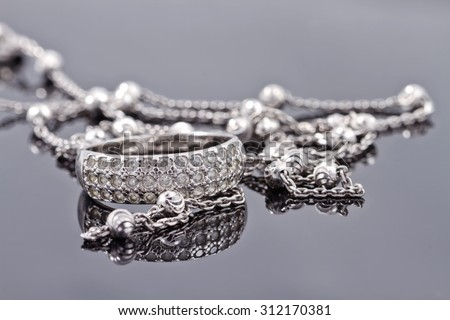 Unusual beautiful silver chain and a silver ring with gems on the reflecting surface - stock photo