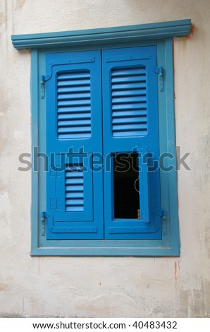 Unusual blue window shutters - stock photo