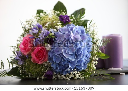 Unusual bridal bouquet with pink roses and blue hydrangeas lying on a table alongside a candle