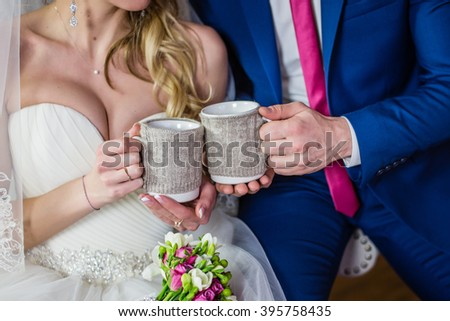 Unusual cups in hands of the bride white at the wedding with her groom vintage - stock photo