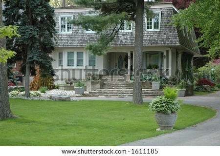 Unusual elegant stucco house with concrete flower urn / planter along driveway - stock photo