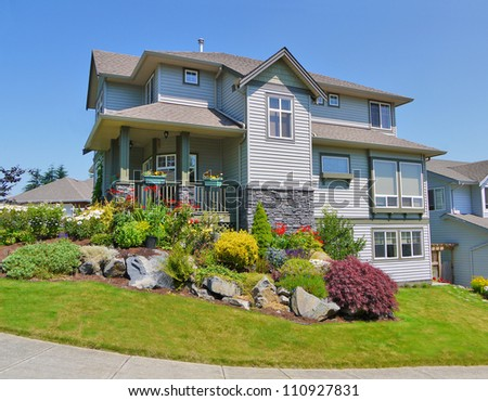 Unusual family house with landscaping on the front and blue sky on background - stock photo