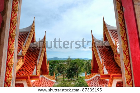 Unusual frame created by two parts of roof of Buddhist temple in Phuket, Thailand - stock photo
