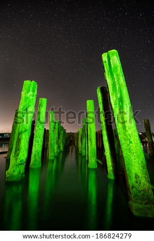 Unusual green poles in the water reflection  at night with deep stars sky - stock photo