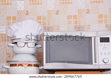 Unusual jesting chef about microwave oven - stock photo
