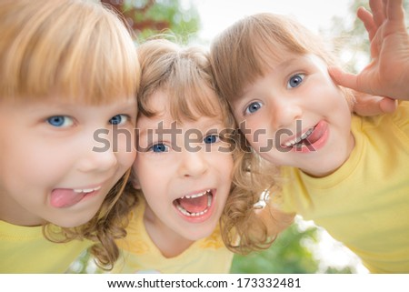 Unusual low angle view portrait of happy children playing outdoors in spring park. Fisheye shot - stock photo