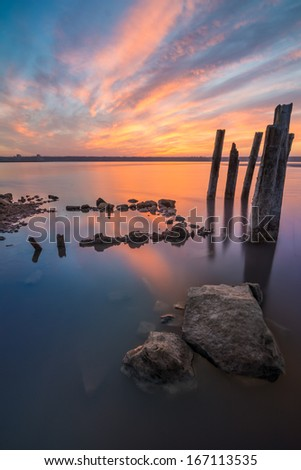Unusual pillars in the water on the background of colorful sky with bright clouds - stock photo