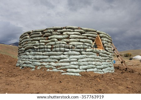 Unusual round house of the bags with soil - stock photo