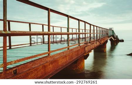 unusual rusty old bridge on the coast of the Black Sea in Ukraine - stock photo