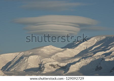 Unusual UFO shaped cloud over the Antarctic mountains sunny winter day. - stock photo