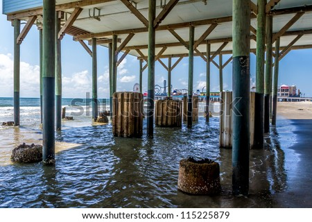 Unusual View of Wooden and Older Concrete Piers Underneath Galveston Beach Structure with Pleasure Pier Carnival on Other Side. - stock photo