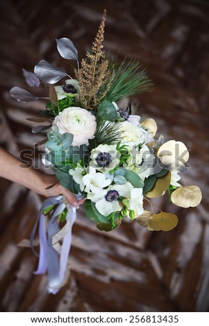 Unusual wedding bouquet with ranunculus, freesia, roses and white anemone in retro style at hands of a bride