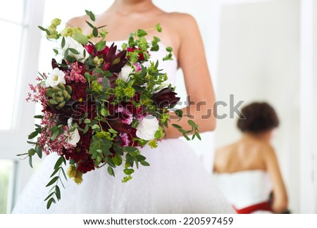 Unusual wedding bouquet with succulent flowers in retro style at hands of a bride