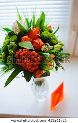 Unusual wedding bouquet with two wedding ring. Bouquet of physalis, rowan, ear of wheat in a glass vase on the white windowsill. Paper Boat next to a vase. - stock photo