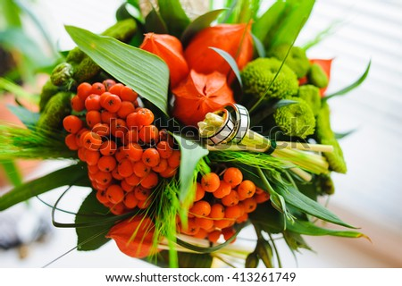Unusual wedding bouquet with two wedding ring. Bouquet of physalis, rowan, ear of wheat in a glass vase on the white windowsill.  - stock photo