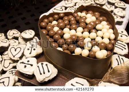 Unusual Wedding Cake with chocolate balls and cupcakes - stock photo
