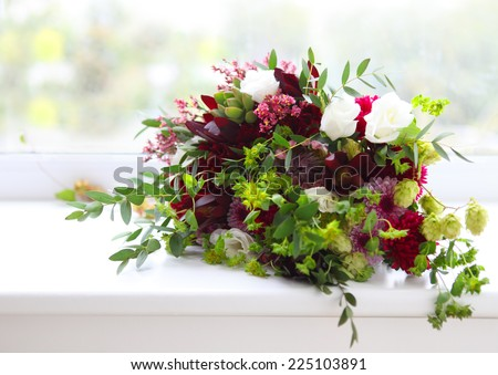 Unusual wedding composition with succulent flowers, fig and hop in retro style near the window - stock photo