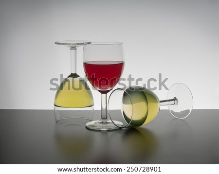 Unusual wine glasses, upright and fallen it seems. Red, white. - stock photo