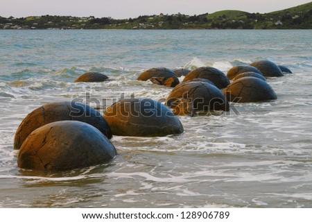 Unusually large and spherical Moeraki boulders lying along the beach on Otago coast, New Zealand - stock photo