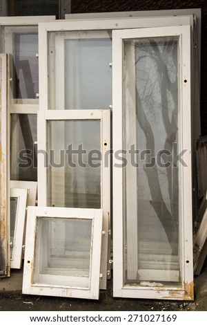 Unwanted window frames with white wood and intact glass - stock photo