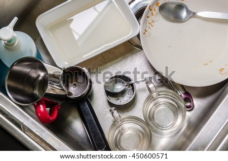Unwashed dishes and utensils in a kitchen sink - stock photo