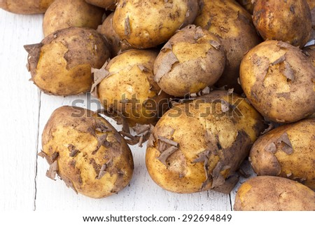 Unwashed new potatoes on white rustic wood. Space for text. - stock photo