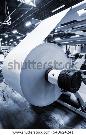 unwinding a roll of paper in a modern printing house.