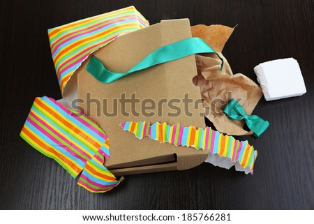 Unwrapped and opened gift box  on wooden background - stock photo