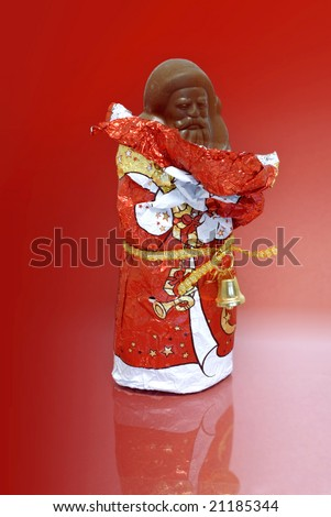 unwrapped chocolate Nikolaus or Santa agianst a red background - stock photo