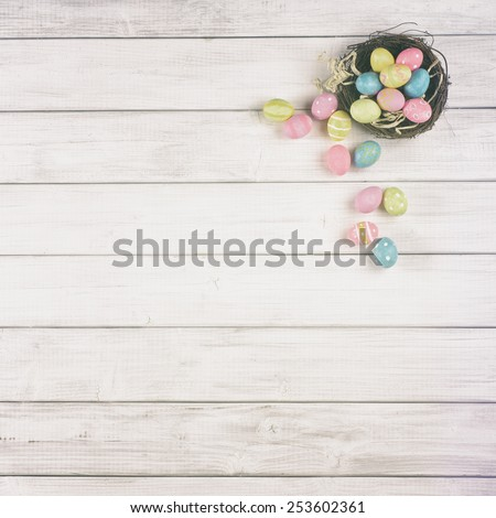 Up Above View Easter Egg Nest Overflowing on Soft Off White or Tan Gray Wood Board Background for room or space for copy, text, your words.  Square can be cropped horizontal or vertical, trendy fade - stock photo