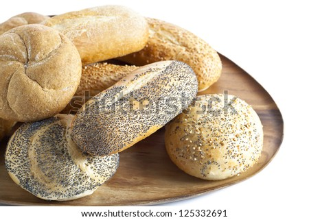 Up close image of loaf of breads on a wooden plate against white background