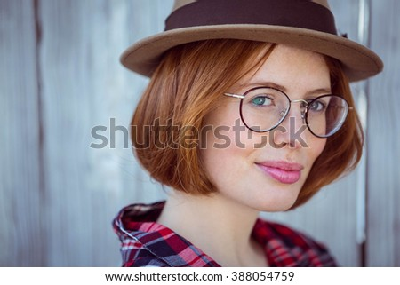 up close portrait of a smiling hipster woman, against a wooden background - stock photo
