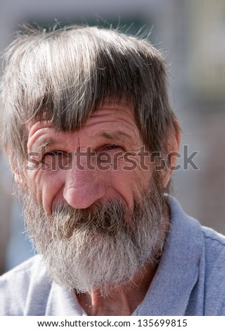Up-close portrait of homeless man outdoors during the day - stock photo