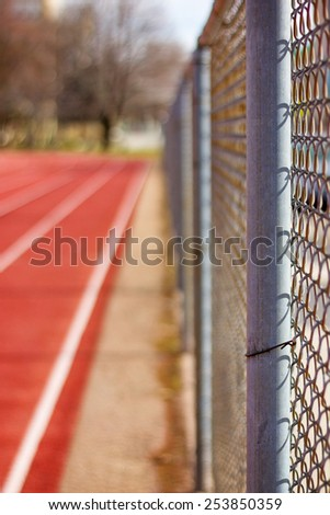 up-close view of chain link fence surrounding a track field separating the road and pedestrians with a retro instagram filter (shallow depth of field) - stock photo