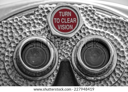 Up close view of old coin-operated binoculars with the words: Turn to Clear Vision - stock photo