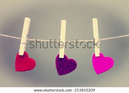 up-close view of three different felt hearts hanging from twine with clothes pins with a instagram filter (shallow depth of field) - stock photo