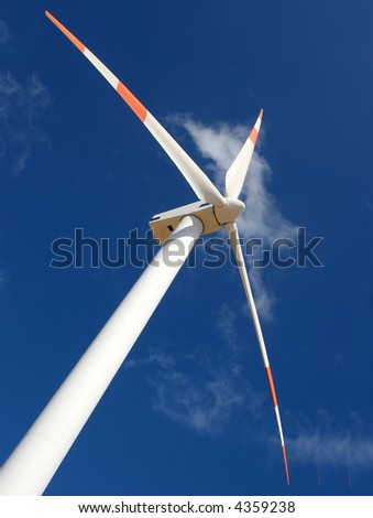up perspective of wind mill power generator against blue sky