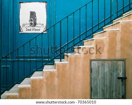 Up the stairs to the second floor and blue wall - stock photo