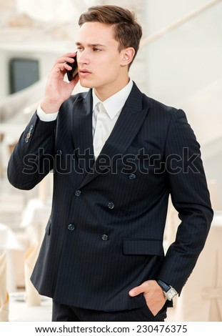 Up to the client. Confident and successful businessman in a strict dress standing in an office and talking on mobile phone while waiting for the client - stock photo