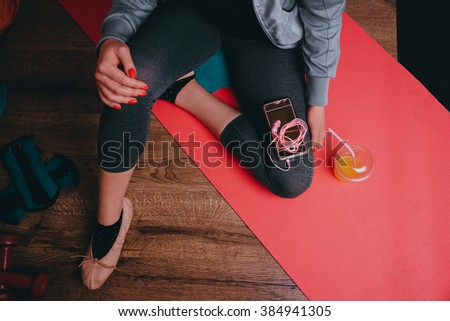 Up view on beautiful young woman in ballet shoes relaxing.Sport equipment, juice, mobile phone on mat/Urban fitness sport and healthy lifestyle concept