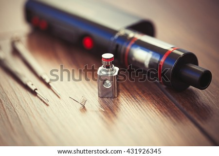Upgrade parts for modern vaporizer e-cig device, spare parts. Modern device model and micro coil clearomizer. Good way to quit smoking nicotine cigarette and improve health. Macro close up - stock photo
