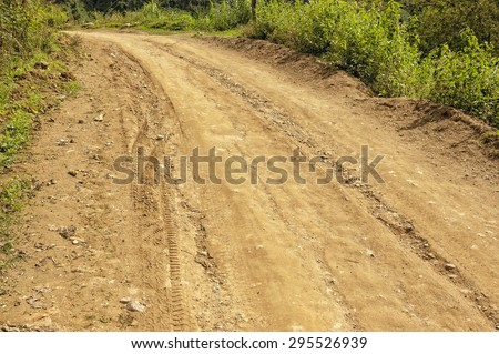 Uphill dirt road with tire tracks and grasses on both sides - stock photo